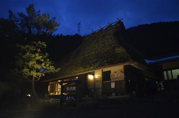 幻想的な雰囲気の茅葺屋根の民家