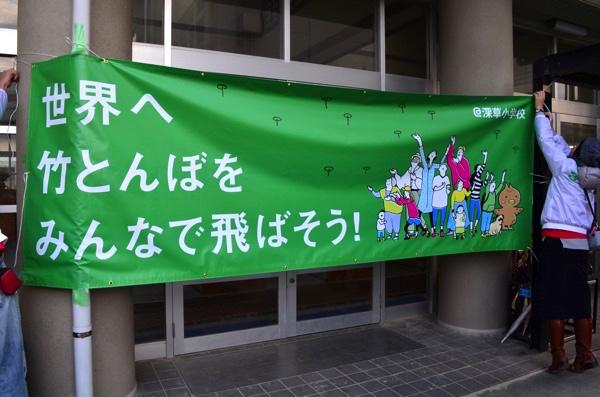 「世界へ竹とんぼをみんなで飛ばそう! 」と書かれた横断幕