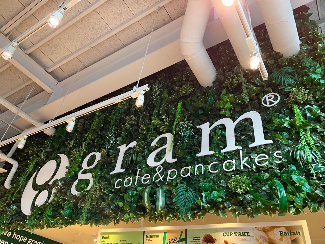 緑色の植物につつまれたgramのロゴ