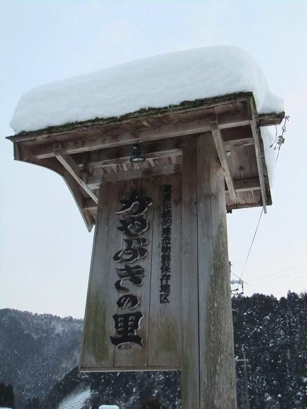 雪が積もるかやぶきの里の看板